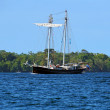 Sailing ship with tropical island in background — Foto Stock