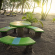 Sunset on beach with round table and benches — Stock Photo