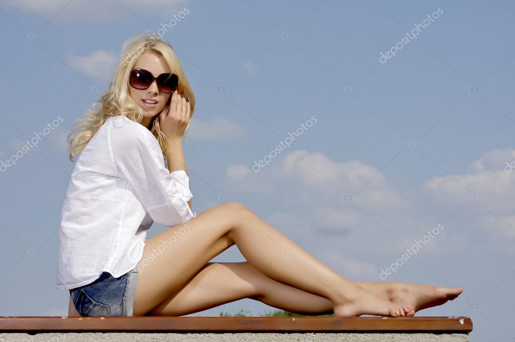 Portrait of beautiful blonde girl in sunglasses on background blue sky — Stock Photo #12470779