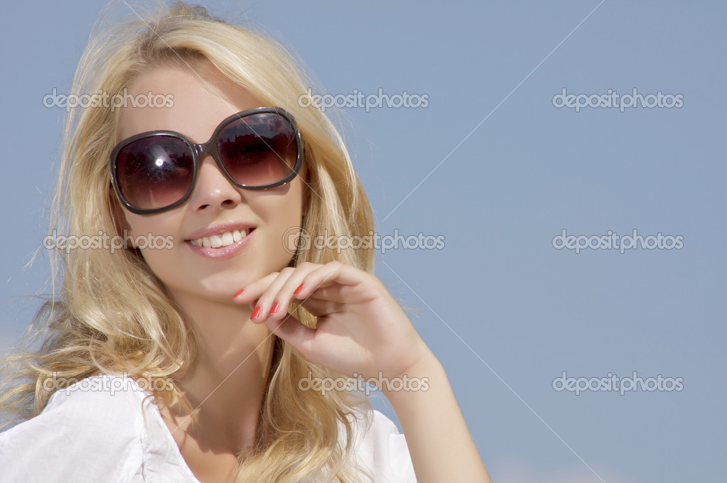 Portrait of beautiful blonde girl in sunglasses on background blue sky — Stock Photo #12470795