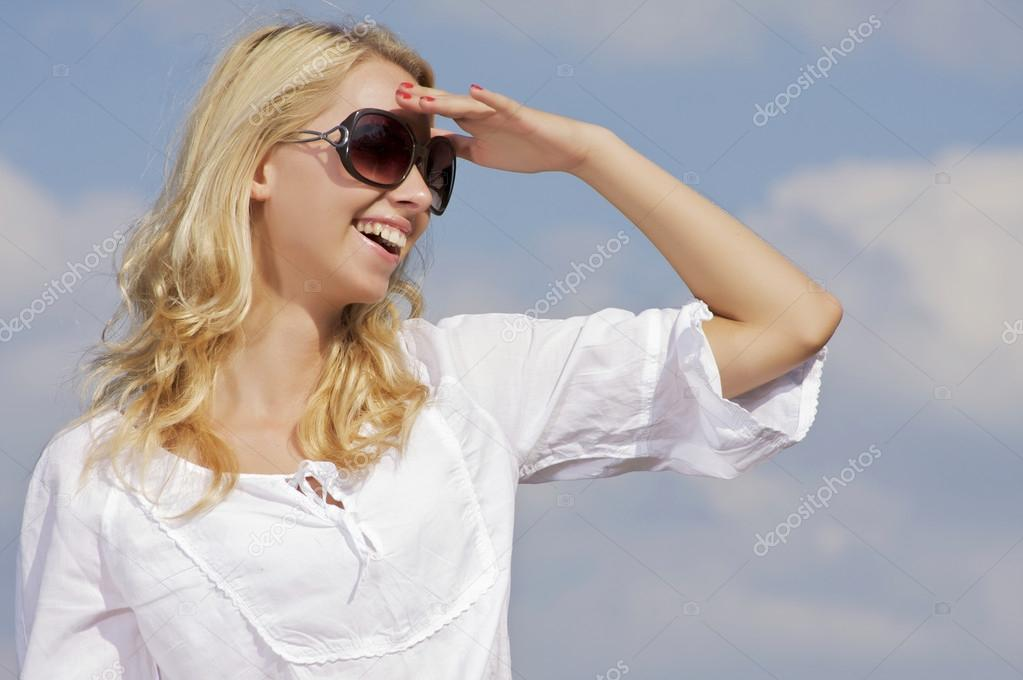Portrait of beautiful blonde girl in sunglasses on background blue sky — Zdjęcie stockowe #12470813
