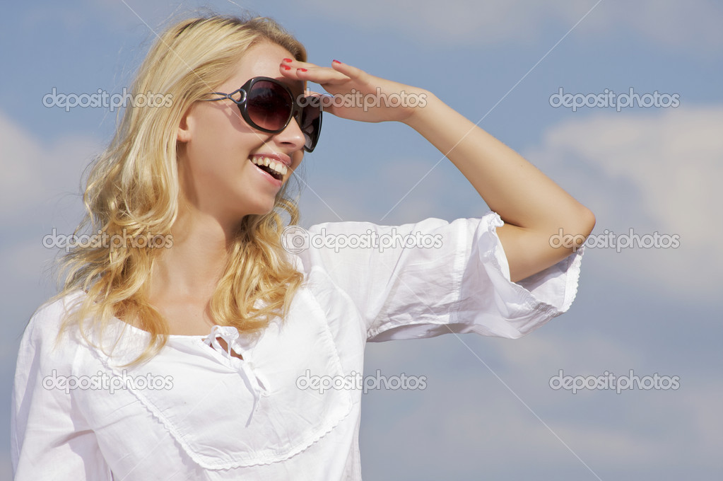 Portrait of beautiful blonde girl in sunglasses on background blue sky  Stock Photo #12470813