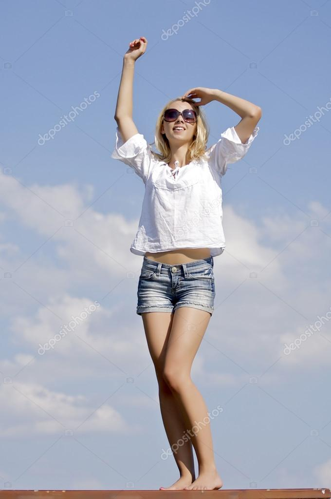 Portrait of beautiful blonde girl in sunglasses on background blue sky — Stock Photo #12470881