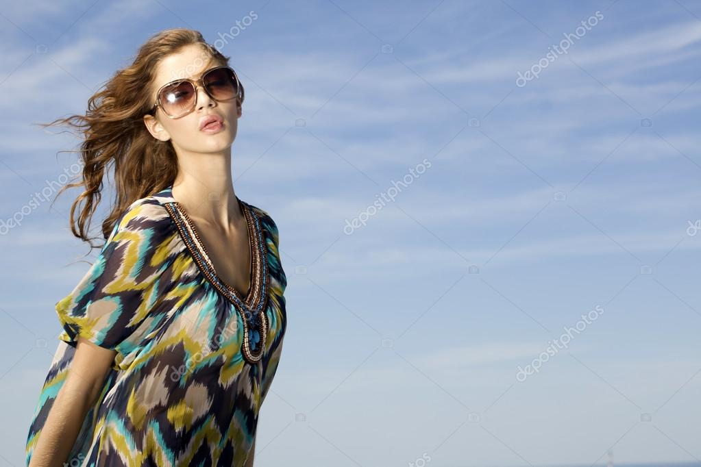 Portrait of beautiful brunette girl in sunglasses on background blue sky — Stock Photo #12471796