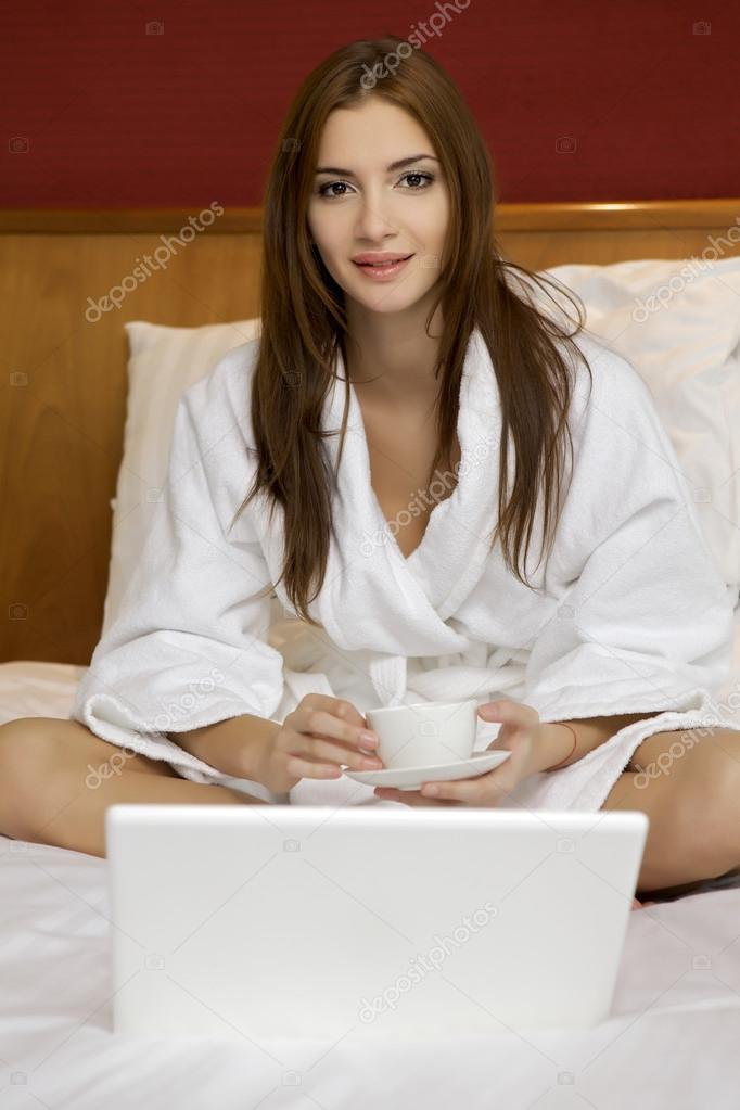 Portrait of beautiful brunette woman with cup on bed at bedroom — Stock Photo #12532060