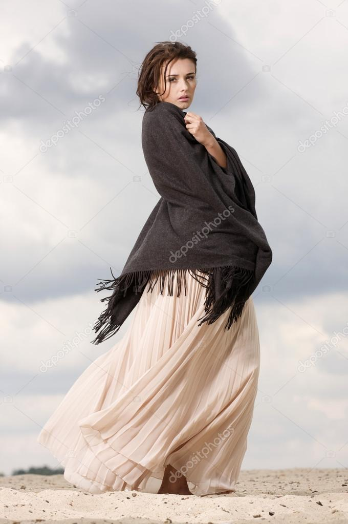 Fashionable young attractive and sensuality brunette woman in white dress dancing on the desert — Stock Photo #12812949