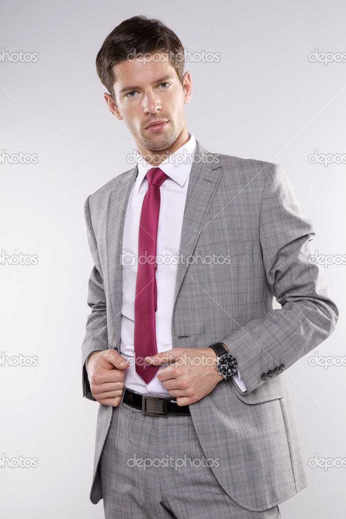 Fashion shot of an elegant young man wearing suit on grey background — Stock Photo #13335125