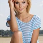 Beautiful girl on background blue sky — Stock Photo