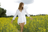 Brunette woman in a yellow flowers field — Stock Photo