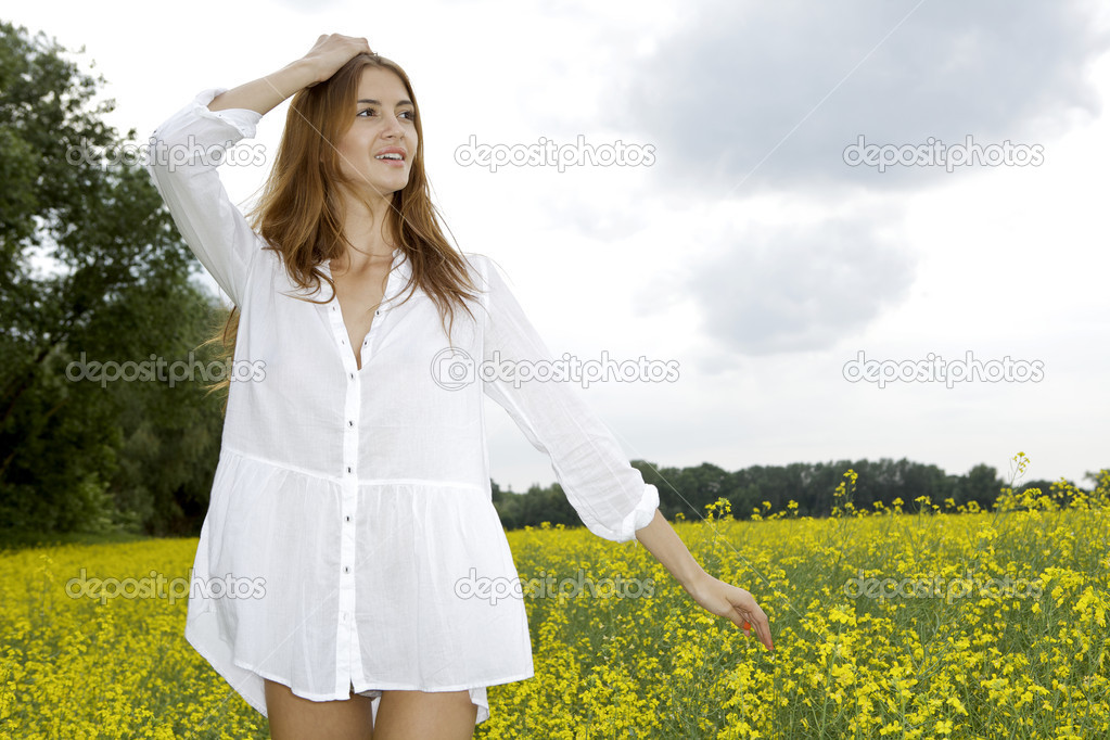 Beautiful and sensuality brunette woman in a yellow flowers field — Stock Photo #18410271