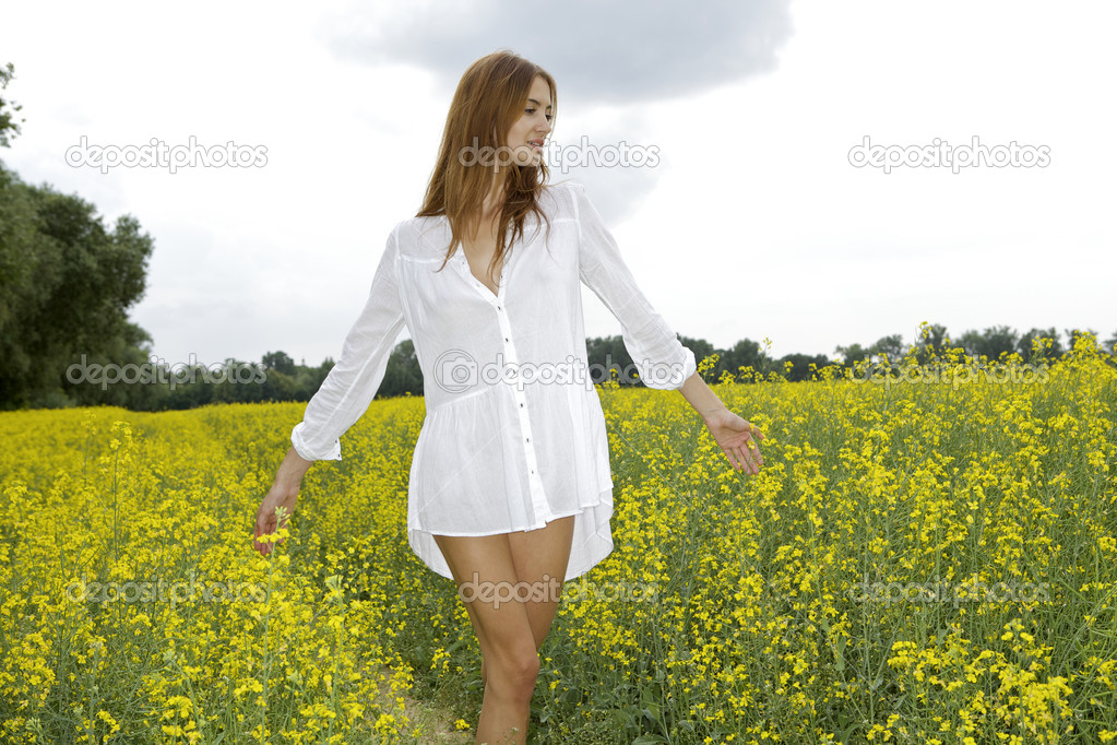 Beautiful and sensuality brunette woman in a yellow flowers field — Stock Photo #18410273