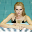 Beautiful young woman standing in a swimming pool - Stock Photo