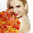 Beautiful blonde girl with the bouquet of tulips isolated on a w - Stock Photo