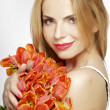Beautiful blonde girl with the bouquet of tulips isolated on a w — Stock Photo