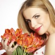 Beautiful blonde girl with the bouquet of tulips isolated on a w — Stock Photo #26517917