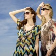 Two beautiful girl in sunglasses on background blue sky — Stock Photo #26518323