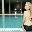 Stock Photo: Beautiful young woman standing in a swimming pool