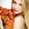 Beautiful blonde girl with the bouquet of tulips isolated on a w — Stock Photo #29090217