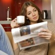 Stock Photo: Mid adult woman drinking coffee and reading news