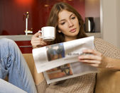 Mid adult woman drinking coffee and reading news — Stock Photo