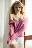 Young slim sexy woman in pink sweater against the window — Stock Photo