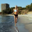 Beautiful young sport woman running on beach. - Stock Photo
