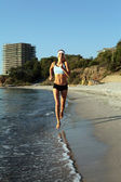 Beautiful young sport woman running on beach. — Stock Photo