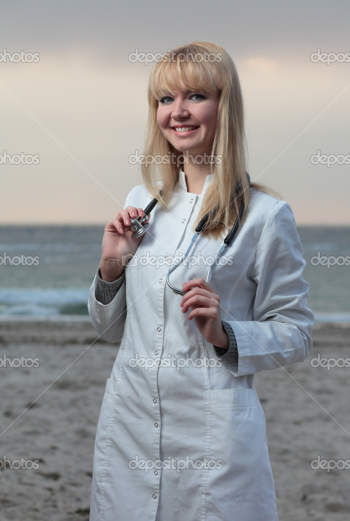 Female doctor smiling on the background of the sea. — Stock Photo #13885231