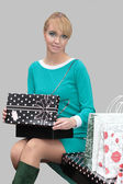 Young woman holding a present and shopping bags. — Stock Photo