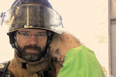 Closeup of a fireman holding a little girl — Stock Photo