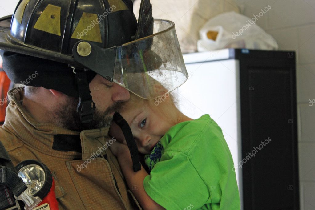 A firefighter holding a young girl — Stock Photo #13863920