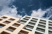 Double color hotel over blue sky with clouds — Stock Photo