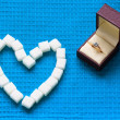 Engagement ring and sugar hearts — Stock Photo