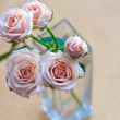 Pink roses in vase on wooden desk — Foto de stock #21700213