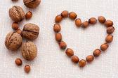 Walnuts, hazelnuts on a wooden background — Stock Photo