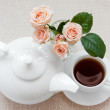 Stock Photo: Teapot, cup, and roses on plate