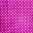 Wrinkled purple cloth with a white dot — Stock Photo