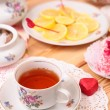 Warm cup of tea, lemon and sweets — Stockfoto #39471473