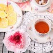 Warm cup of tea, heart shaped cake and sweets — Stockfoto #39472107