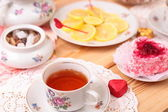 Warm cup of tea, lemon and sweets — Stock Photo