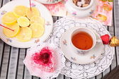 Warm cup of tea, heart shaped cake and sweets — Stock Photo
