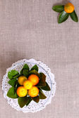 Fresh citrus fruits in vase on the linen cloth — Stock Photo