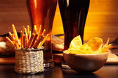 Glasses of beer with chips and snacks — Stock Photo