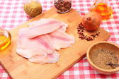 Raw fish tilapia on cutting board and spices — Stok fotoğraf