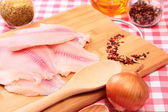 Raw fish tilapia on cutting board and spices — Stock Photo