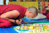 Tibetian monks constructing mandala from colored sand — Stock Photo
