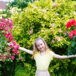 Portrait girl and rose bushes — Stock Photo