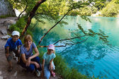 Family near summer azure limpid transparent lake (Plitvice, Cr — Stock Photo