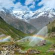 Stock Photo: Rainbows in irrigation water spouts in Summer Alps mountain