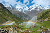 Rainbows in irrigation water spouts in Summer Alps mountain — Stock Photo
